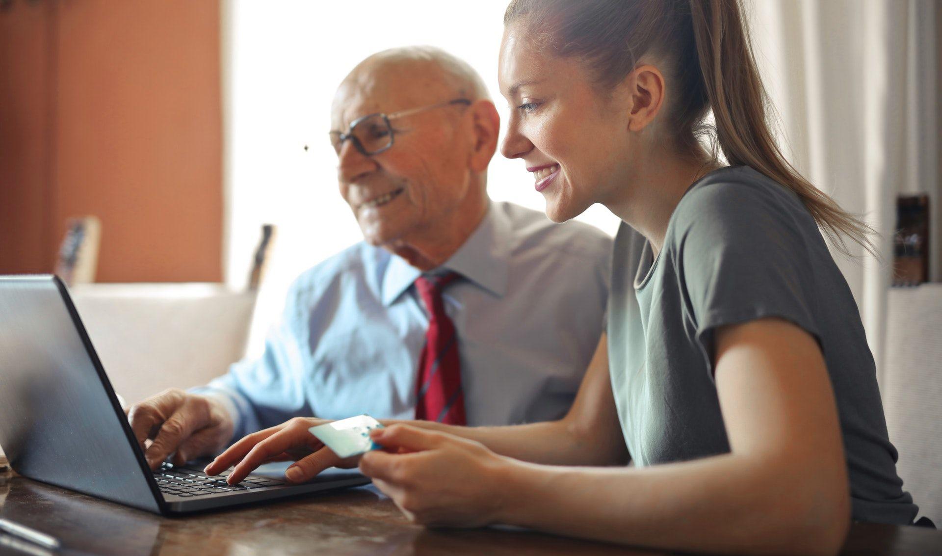Senior gibt Azubi nachhilfe am Computer