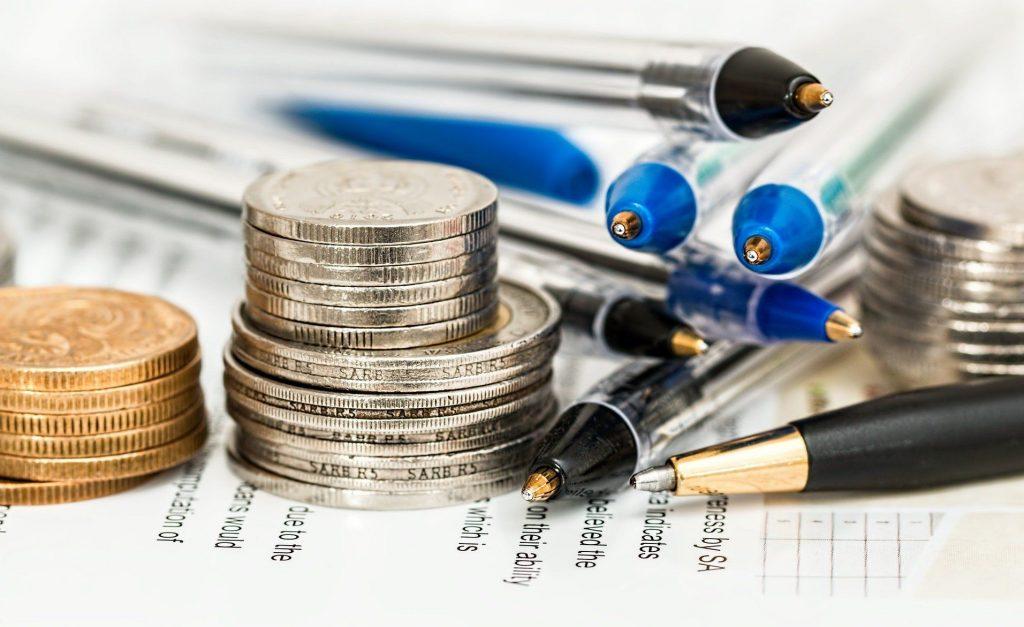 Nahaufnahme von Münzstapeln und Stiften auf einer Rechnung
