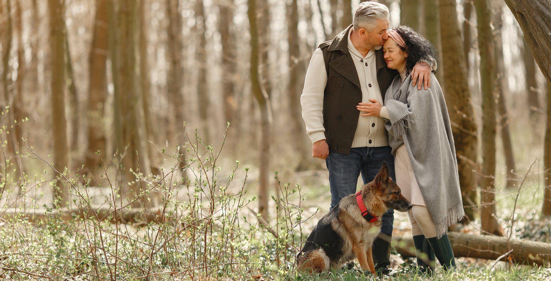 Älteres, verliebts Pärchen mit Hund hält sich im Wald im Arm