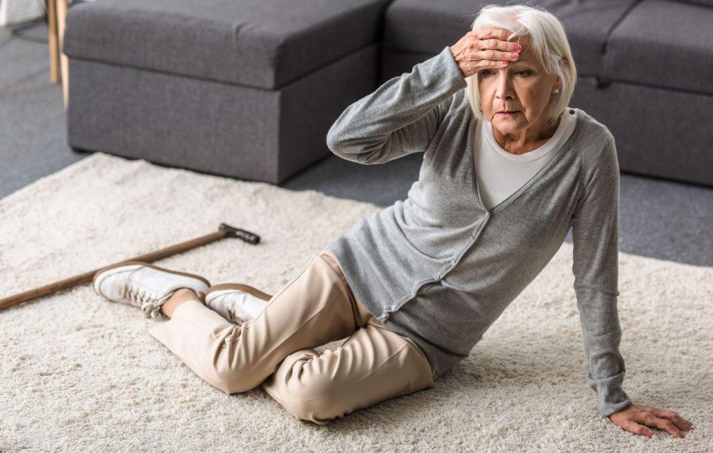 Senior Frau sitzt auf dem Teppich und hält sich die Stirn
