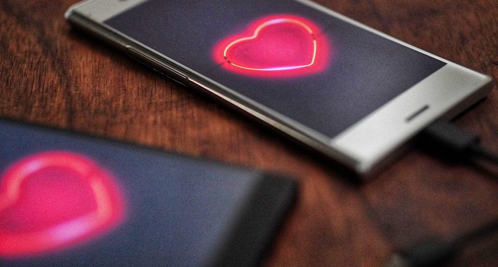 Zwei Handys mit Herz im Display auf dem Holtzisch