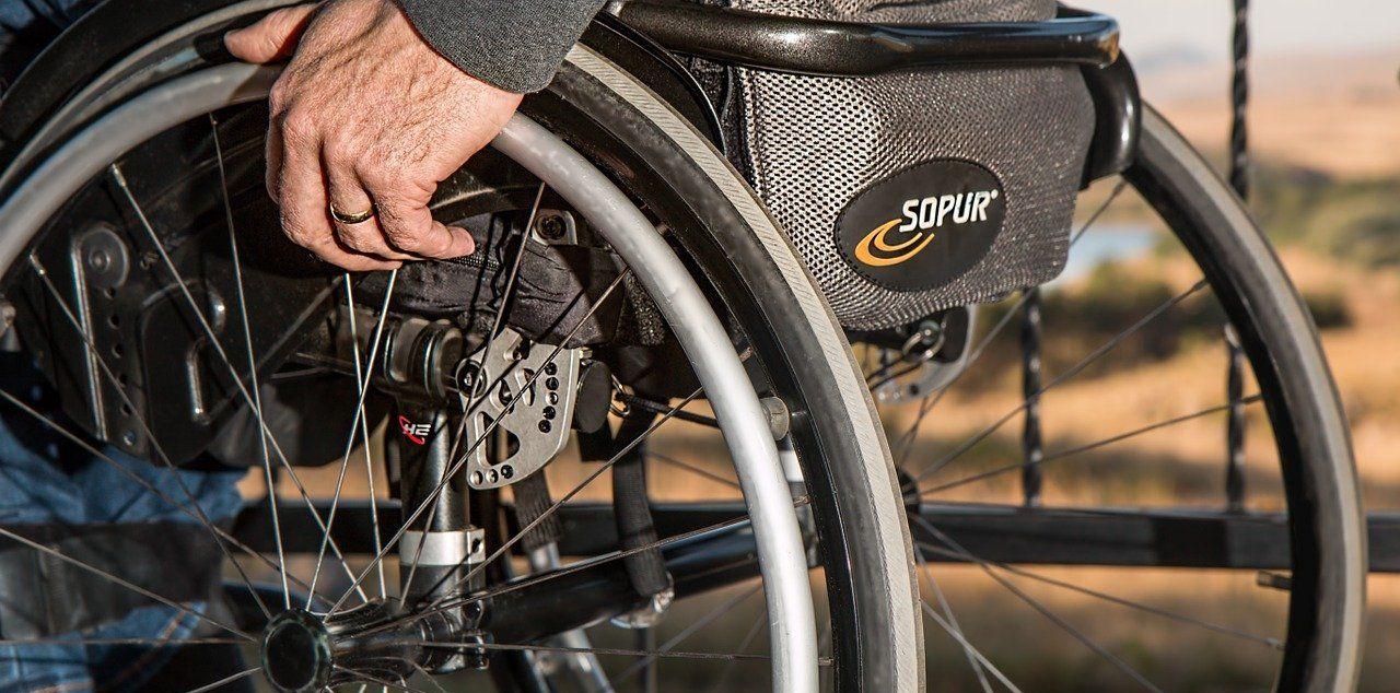 Rollstuhlfahrer fährt, mit Fokus auf die Räder
